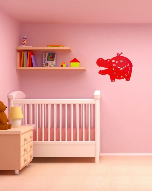 Red accent clock in pink nursery
