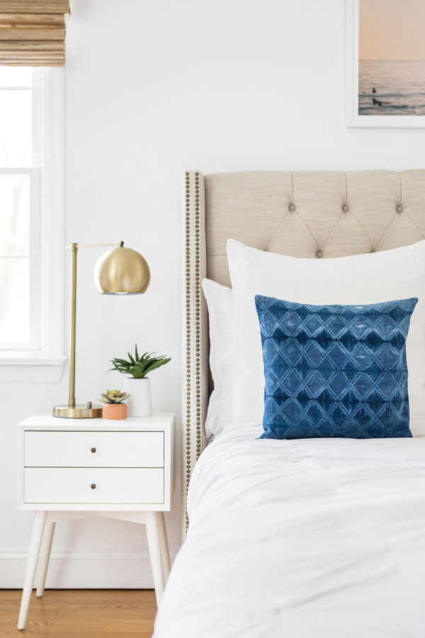 White bedding with blue decorative pillow