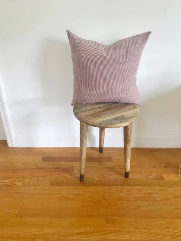 Pink textured decorative pillow on stool