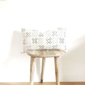 Wooden stool with white and black mud cloth throw pillow