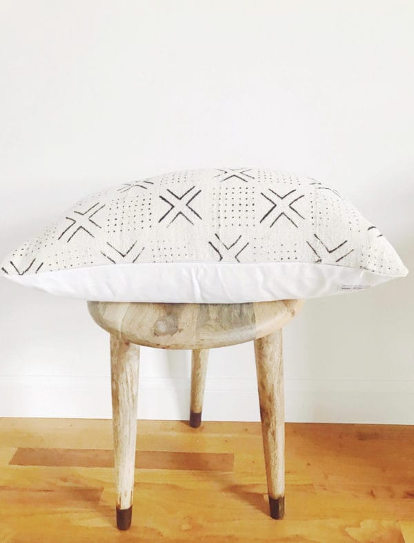 Wooden stool with white patterned decorative pillow