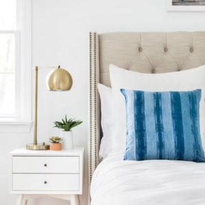 White bed with blue striped throw pillow