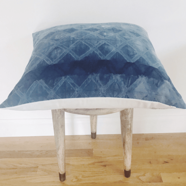 Wooden stool with blue decorative pillow