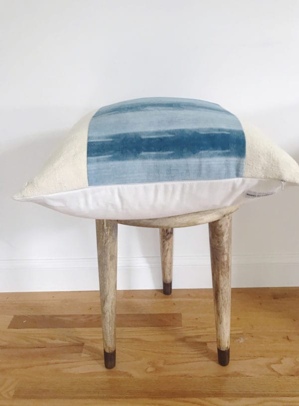 Wooden stool with blue patterned pillow