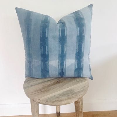 Wooden stool and blue striped throw pillow