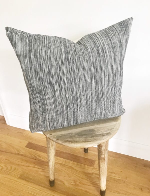 Wooden stool with textured black and white pillow